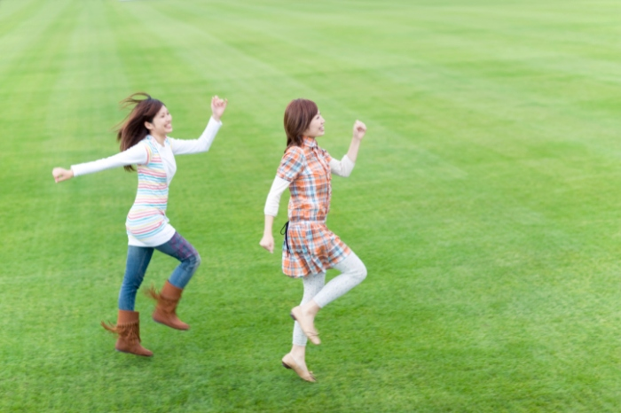 Two young women skipping on sports field