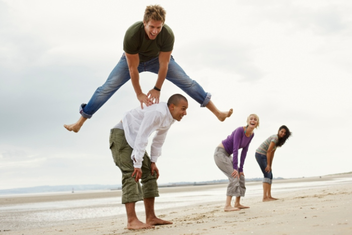 Young Friends Playing Leapfrog on Beach